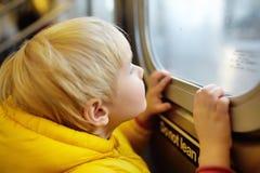 El niño pequeño mira hacia fuera la ventana del coche en el subterráneo en Nueva York foto de archivo