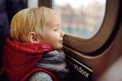 El niño pequeño mira hacia fuera la ventana del coche en el subterráneo en Nueva York fotografía de archivo