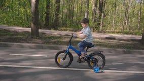 El niño pequeño monta la bici a lo largo del parque de la ciudad pequeño ciclista que monta la bicicleta azul almacen de metraje de vídeo