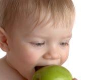 El niño pequeño muerde una manzana verde Imágenes de archivo libres de regalías