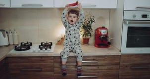 El niño pequeño muy lindo se sienta en la cocina que juega con las verduras una y la sonrisa Epopeya roja almacen de metraje de vídeo