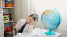 El niño pequeño no quiere aprender y estudiar el mapa del mundo HD 1080 almacen de video