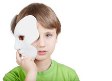 El niño pequeño oculta la mitad de la cara detrás de la máscara Fotos de archivo