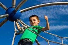 El niño pequeño orgulloso sube la estructura del juego en el patio foto de archivo libre de regalías