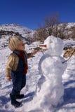 El niño pequeño, pelo rubio, jugando en invierno con nieve, construye el muñeco de nieve Vaqueros y bufanda que llevan Imagenes de archivo