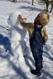 El niño pequeño, pelo rubio, jugando en invierno con nieve, construye el muñeco de nieve Vaqueros y bufanda que llevan Foto de archivo libre de regalías