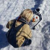 El niño pequeño, pelo rubio, jugando en invierno con nieve, construye el muñeco de nieve Vaqueros y bufanda que llevan Fotografía de archivo libre de regalías