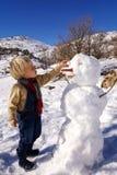 El niño pequeño, pelo rubio, jugando en invierno con nieve, construye el muñeco de nieve Vaqueros y bufanda que llevan Imagen de archivo