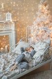 El niño pequeño pone en un cuarto con el árbol de navidad Imágenes de archivo libres de regalías