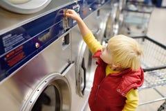 El niño pequeño pone la moneda en la secadora en el lavadero público imagen de archivo libre de regalías