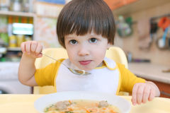 El niño pequeño precioso come la sopa Foto de archivo libre de regalías