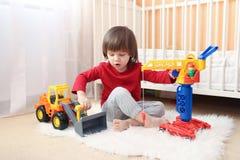 El niño pequeño precioso juega los coches Foto de archivo libre de regalías