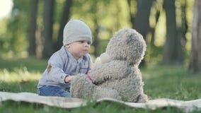 El niño pequeño que juega con el peluche refiere una sobrecama en parque almacen de metraje de vídeo