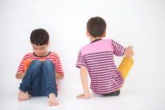 El niño pequeño que juega la tableta y otro quieren no jugar con el muchacho ninguna atención Imagenes de archivo
