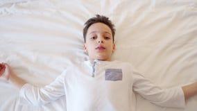 El niño pequeño que juega, se cae dormido en cama antes de hora de acostarse almacen de metraje de vídeo