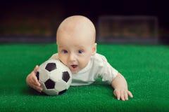 El niño pequeño que miente en la hierba con la bola foto de archivo libre de regalías