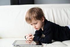 El niño pequeño que miente en su estómago y mira una película en la tableta Fotografía de archivo