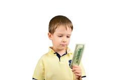 El niño pequeño que mira la cuenta 100 dólares de EE. UU. y piensa a lo que Imagen de archivo libre de regalías