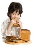 El niño pequeño que que come un pan en el escritorio Fotografía de archivo