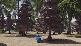 El niño pequeño que se sienta debajo de los árboles de navidad hechos de los materiales reciclados de la palma vieja ramifica almacen de metraje de vídeo