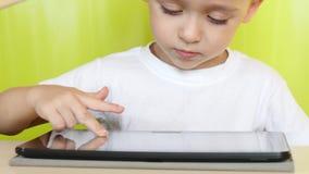 El niño pequeño que se sienta en la tabla toca la visualización electrónica de la tableta Un niño está jugando con un ordenador p almacen de video