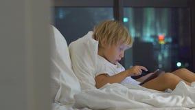 El niño pequeño que se sienta en su cama en la noche juega una PC de la tableta con las siluetas de un rascacielos en un fondo almacen de metraje de vídeo