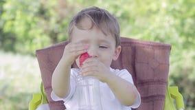 El niño pequeño que se sienta en una tabla en la naturaleza bebe el agua de una botella almacen de video