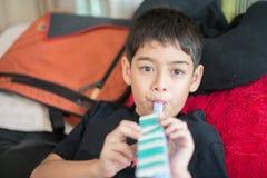 El niño pequeño que toca la flauta coloca en la cama imagen de archivo libre de regalías