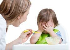 El niño pequeño rechaza comer la cara cerrada por las manos Fotografía de archivo