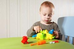 El niño pequeño repara el automóvil Imagen de archivo libre de regalías