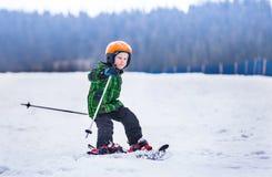 El niño pequeño resbala en los esquís abajo a lo largo de la cuesta de la nieve Imagen de archivo libre de regalías