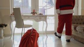El niño pequeño roba el bolso de Santa Claus con los presentes almacen de video