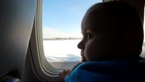 El niño pequeño rubio se sienta cerca de ventana y de miradas del aeroplano almacen de metraje de vídeo