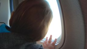 El niño pequeño rubio se sienta cerca de ventana y de miradas del aeroplano almacen de video
