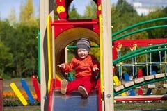 El niño pequeño rubio se sienta en una diapositiva de los niños en el patio Fotos de archivo libres de regalías