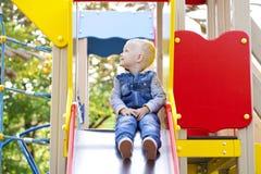 El niño pequeño rubio se sienta en una diapositiva de los niños en el patio Imagen de archivo libre de regalías