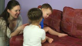 El niño pequeño rueda la máquina en el sofá El jugar feliz de la familia almacen de video