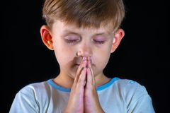 El niño pequeño ruega a dios con sus manos dobladas Primer en un fondo negro Imagenes de archivo