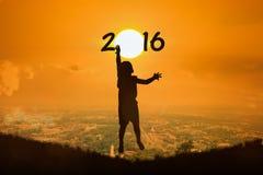 El niño pequeño salta el Año Nuevo 2016 de la puesta del sol del tacto Fotos de archivo libres de regalías