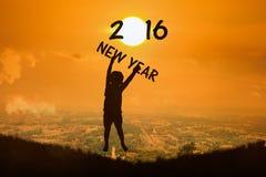 el niño pequeño salta la puesta del sol 2016 del Año Nuevo del texto de la demostración b Fotos de archivo