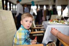El niño pequeño sano lindo come la sandía que se sienta en café dentro Imágenes de archivo libres de regalías