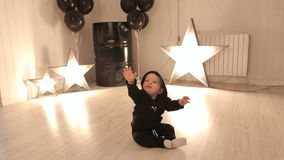 El niño pequeño se está sentando en el piso del estudio contra un fondo de estrellas que brillan intensamente almacen de metraje de vídeo
