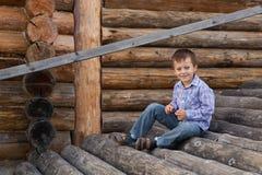 El muchacho lindo se está sentando en registros Fotografía de archivo