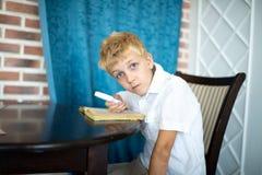 El niño pequeño se está sentando en una tabla que mira a través de una lupa fotografía de archivo