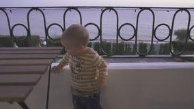 El niño pequeño se relaja en el balcón del hotel metrajes