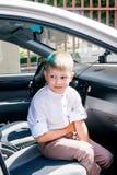 El niño pequeño se sienta en coche mientras que en resto y espera continuatio foto de archivo