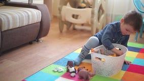 El niño pequeño se sienta en el piso y los juegos con los diversos animales almacen de metraje de vídeo