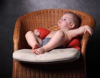 el niño pequeño se sienta en una butaca imagenes de archivo