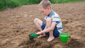 El niño pequeño serio cava un hoyo con una pala Cabrito que juega en la playa almacen de video