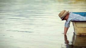 El niño pequeño solo miente en el barco y la mirada en agua metrajes